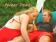 saucy Amber Peach blows cock licking its hard ball by the pool outdoors