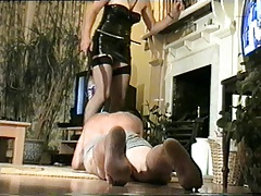 Cruel lady with whip trains slave.
