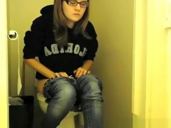 Girl in glasses pees in bathroom toilet