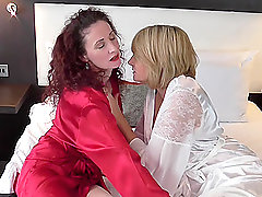 Mature British lesbians Amy and Scarlet masturbate lying in the bed