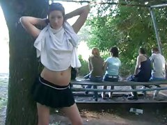 Fabulous white brunette girl in the park flashes her goodies behind the tree