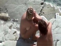 Busty nudist gives head in beach