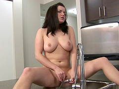 Julie washes her big natural tits and shaved pussy in the kitchen